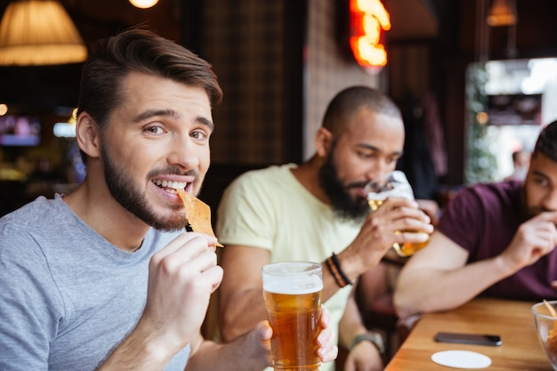 Amigos varones bebiendo cerveza y comiendo patatas fritas en el pub
