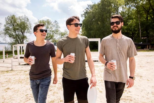 Amigos varones caminando con cerveza