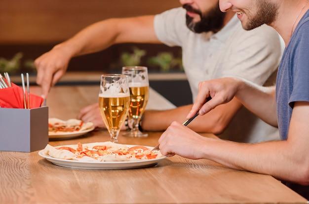 Amigos varones cortando pizza con tenedor y cuchillo en pizzería.