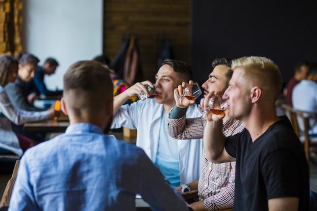 Amigos varones disfrutando de bebidas en el bar