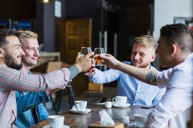 Amigos varones disfrutando de bebidas por la noche en el bar