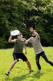 Amigos varones disfrutando de juego de frisbee en el parque
