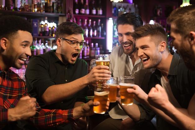 Amigos varones felices tintinean con jarras de cerveza en pub