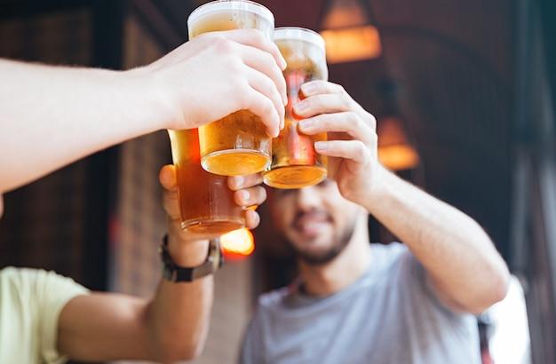 Amigos varones felices tintineo con jarras de cerveza en el pub