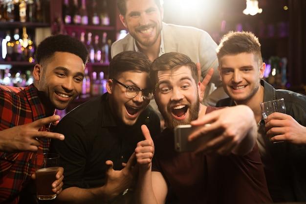 Amigos varones felices tomando selfie y bebiendo cerveza