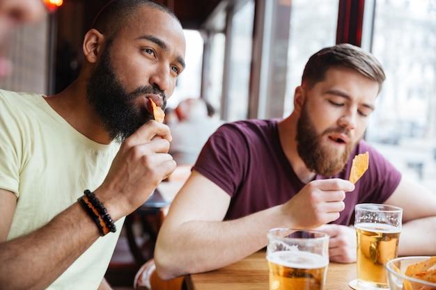 Amigos varones guapos bebiendo cerveza y comiendo patatas fritas en el pub