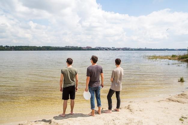 Amigos varones de pie mirando al río