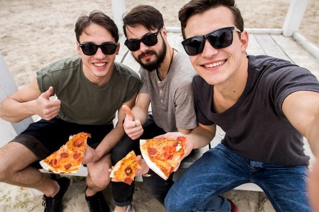 Amigos varones tomando selfie con pizza