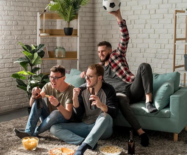 Amigos varones viendo deportes en la televisión y bebiendo cerveza con bocadillos