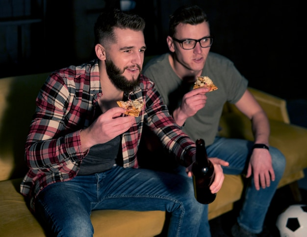 Amigos varones viendo deportes en la televisión juntos mientras toman cerveza y pizza