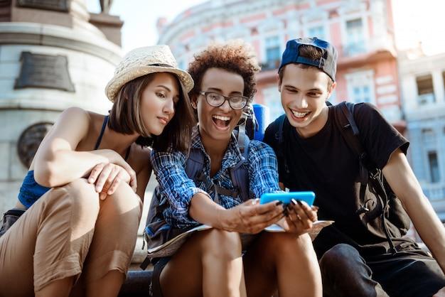 Amigos viajeros con mochilas sonriendo, haciendo selfie, sentados cerca de la vista.