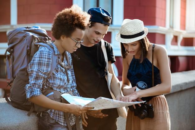 Amigos viajeros con mochilas sonriendo, mirando la ruta en el mapa en la calle.