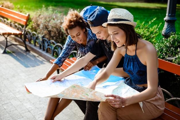 Amigos viajeros sonriendo, mirando la ruta en el mapa, sentado en el banco.