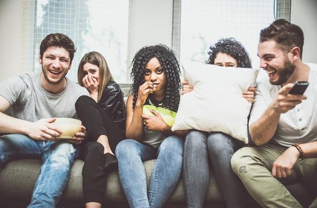 Amigos viendo la película de terror salpicaduras en casa