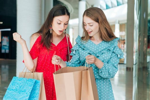 Amigos de la vista frontal con bolsas de la compra.