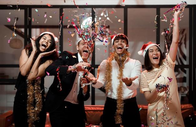 Amigos de vista frontal celebrando en la fiesta de fin de año