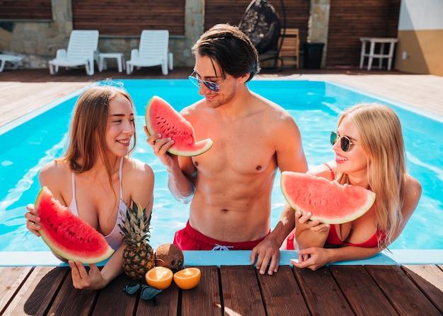 Amigos de la vista frontal comiendo sandía en la piscina
