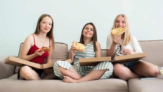 Amigos de la vista frontal disfrutando de una pizza