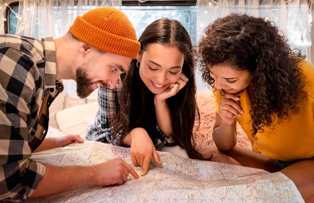 Amigos de vista frontal mirando en un mapa