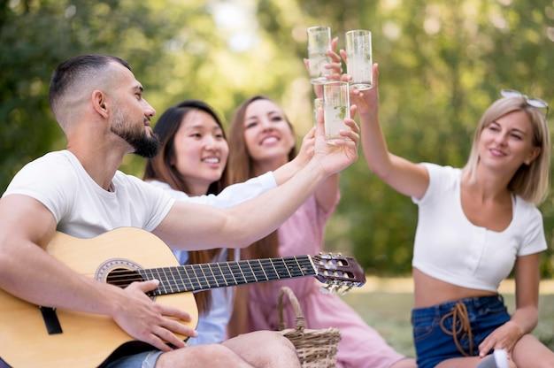 Amigos de vista frontal relajarse después de la pandemia con un vaso de limonada