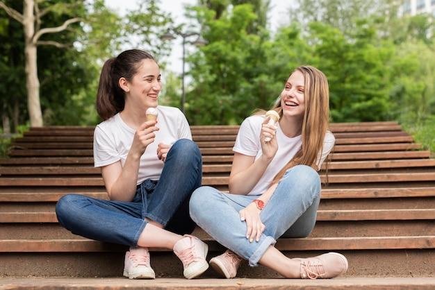 Amigos de la vista frontal sentados en las escaleras mientras comen helado