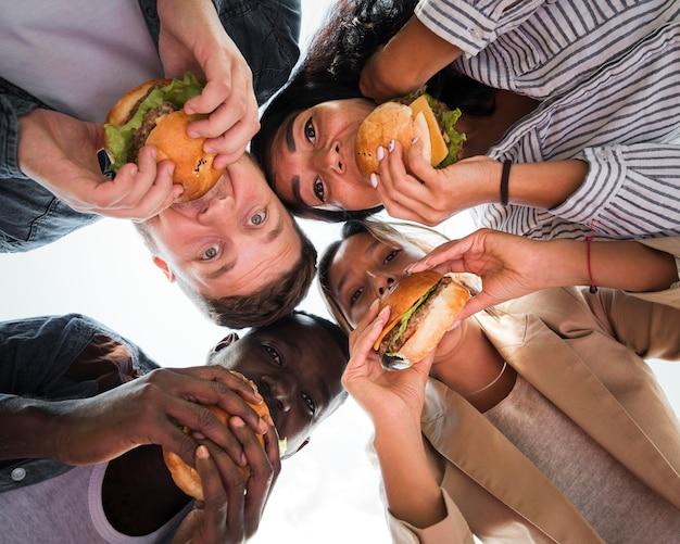 Amigos de vista inferior comiendo hamburguesas