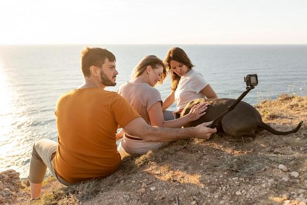Amigos de vista lateral tomando un selfie en una costa