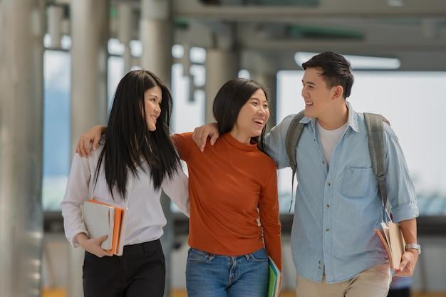 Amistad en el campus, los estudiantes universitarios con libros pasan tiempo juntos.