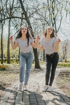 Amistad día dos chicas adolescentes divirtiéndose en el parque