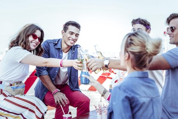 Amistad internacional. increíbles jóvenes sentados en la azotea y bebiendo cerveza Foto Premium