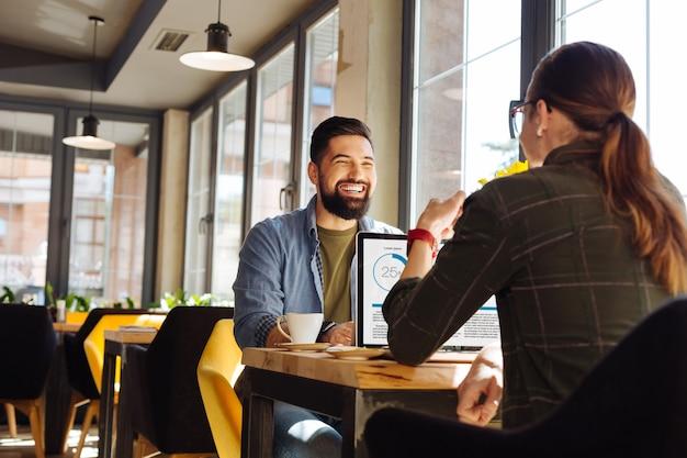 Amistad masculina. hombre alegre encantado sonriendo a su amigo mientras trabaja junto con él