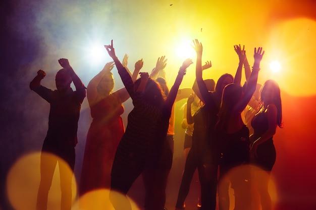 Amistad. una multitud de personas en silueta levanta sus manos en la pista de baile sobre fondo de luz de neón. vida nocturna, club, música, baile, movimiento, juventud. colores amarillo-azul y niñas y niños en movimiento.