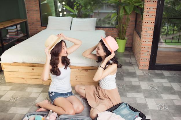 Amistad. viaje. dos amigas asiáticas jóvenes empacando una bolsa de viaje antes de irse de vacaciones