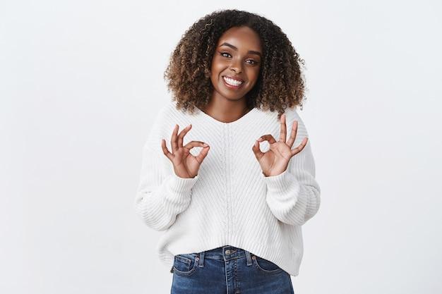 Amistosa, alegre, linda, afroamericana, mujer regordeta, sonriente, encantada, espectáculo, ok, gesto de aprobación, como recomendar servicio, buen trabajo, decir que no hay problema, asegurar que está bien, pared blanca