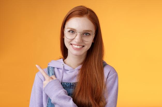 Amistosa atractiva joven pelirroja moderna apuntando con el dedo índice izquierdo mostrando un lugar impresionante que sugiere ir a pasar el rato sonriendo alegremente hablando casualmente discutir nuevo producto, fondo naranja.