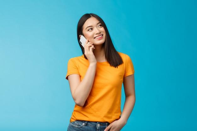Amistosa linda chica asiática urbana busca soñadora relajada, sonriendo alegremente sostenga el teléfono inteligente cerca de la oreja, hablando casualmente con un amigo por teléfono, buena conexión móvil satisfecha, soporte fondo azul.