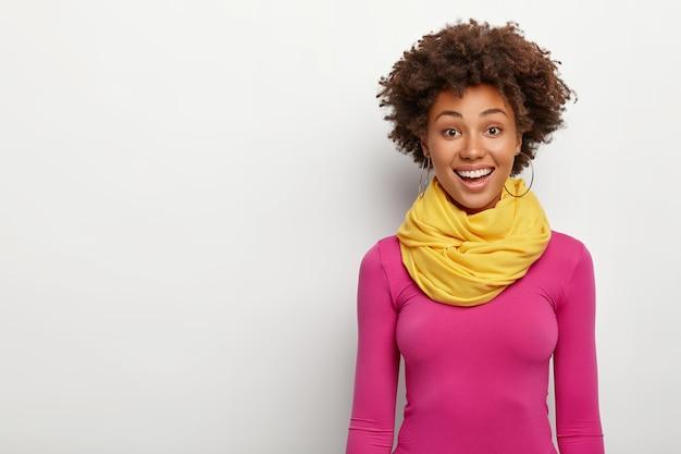 Amistosa mirada alegre chica afro vestida con ropa de moda brillante, sonríe ampliamente