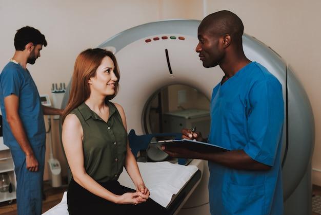 Amistoso doctor comforts paciente tc diagnóstico.