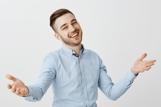 Amistoso hombre de negocios feliz saludando a los nuevos empleados, levantando las manos en una cálida bienvenida