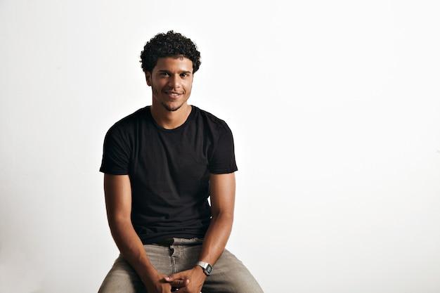 Amistoso joven sonriente en camiseta negra de algodón sin etiqueta y jeans sentado en una silla aislada en blanco
