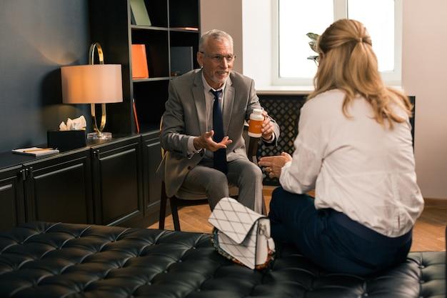 Amistoso psicólogo senior sosteniendo una caja de pastillas en su mano sonriendo y hablando con su paciente