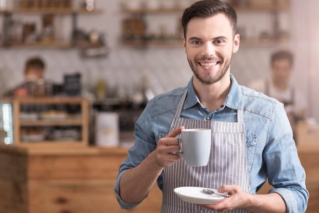 Amo esta bebida apuesto joven agradable sonriendo y sosteniendo una taza de café mientras está de pie en un café.