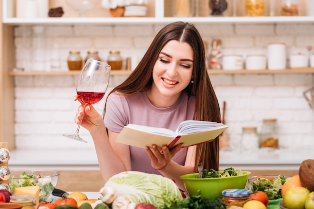 Amo la cocina. blogger de nutrición equilibrada. mujer joven sonriente con copa de vino tinto. libro de recetas saludables en manos.