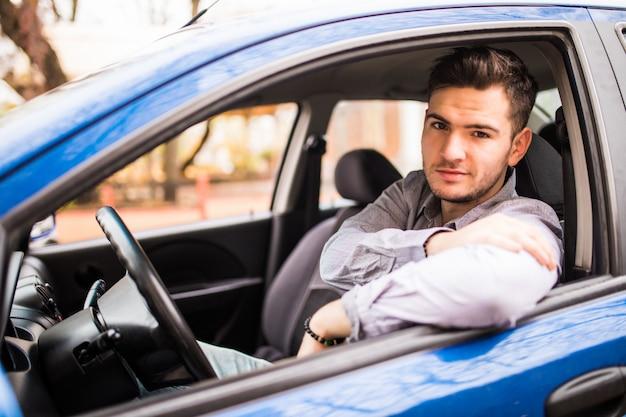 Amo mi carro. apuesto joven conducía su automóvil y sonriendo a la cámara