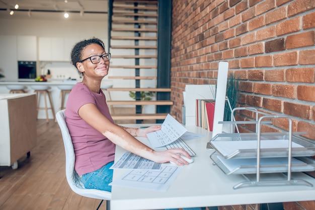 Amo mi trabajo. una mujer en anteojos trabajando en una computadora y mirando contenta