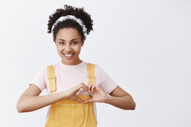 Amo a mis fans. retrato de linda bloguera joven despreocupada y segura con piel oscura en peto amarillo y diadema, mostrando el signo del corazón sobre el pecho y sonriendo con expresión cariñosa y coqueta