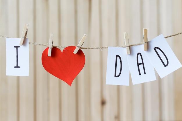 Amo a papa mensaje del día del padre con un corazón de papel colgando con alfileres sobre un tablero de madera ligero
