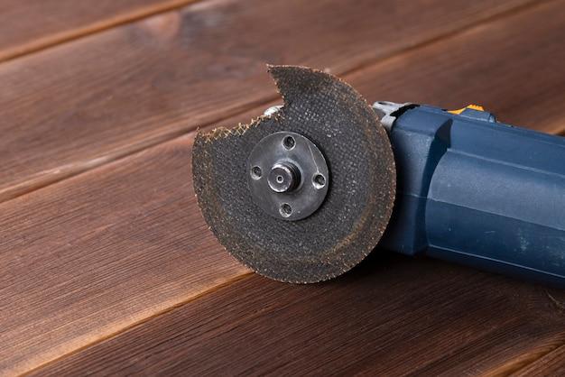 Una amoladora con una cuchilla rota en una mesa de madera. el peligro de usar herramientas eléctricas
