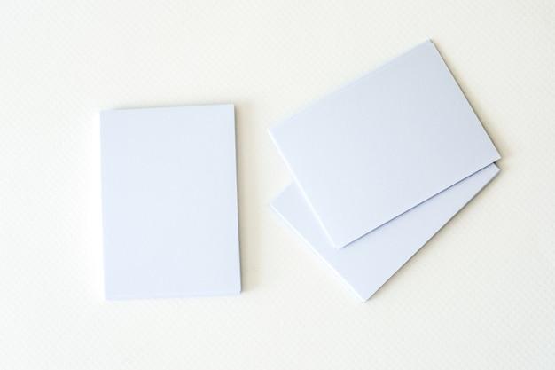 Amontonamiento de la tarjeta de visita blanca vacía de la maqueta en un fondo del libro blanco