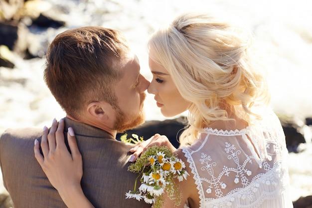 Amor y abrazos de hombre y mujer, relación y amor cercanos, pareja de enamorados en las rocas cerca del río, besándose y abrazados en el chorro de agua